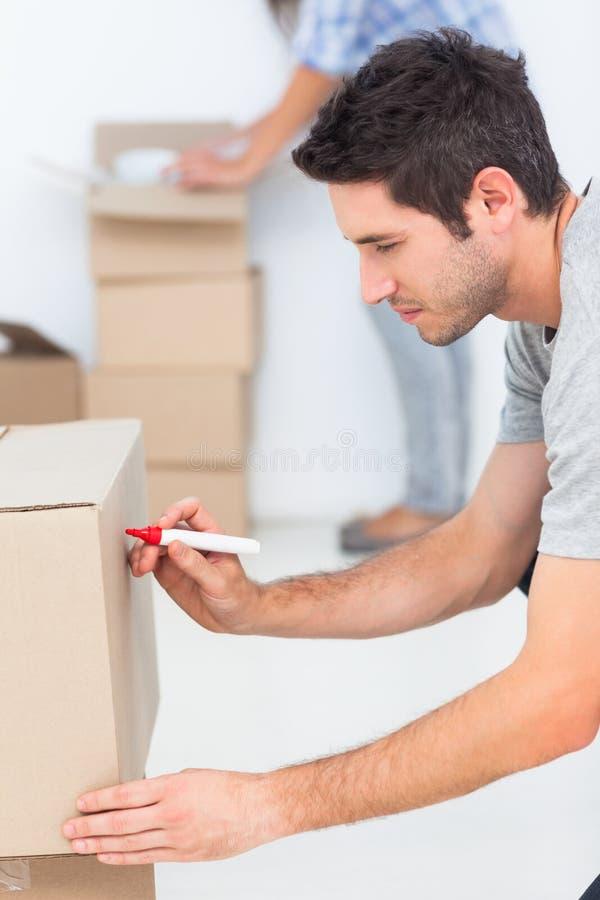 Escrita do homem em uma caixa movente imagem de stock royalty free