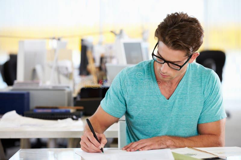 Escrita do homem na mesa no escritório criativo ocupado imagens de stock