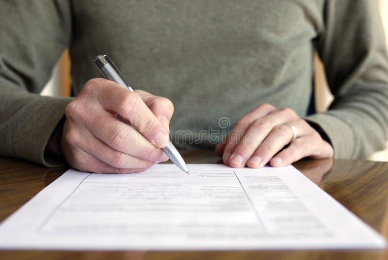 Escrita do homem no papel com a pena na tabela imagens de stock