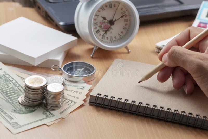 Escrita do lápis do uso da mão na nota do papel e no local de trabalho do negócio dos objetos da finança do negócio na tabela do  fotos de stock royalty free