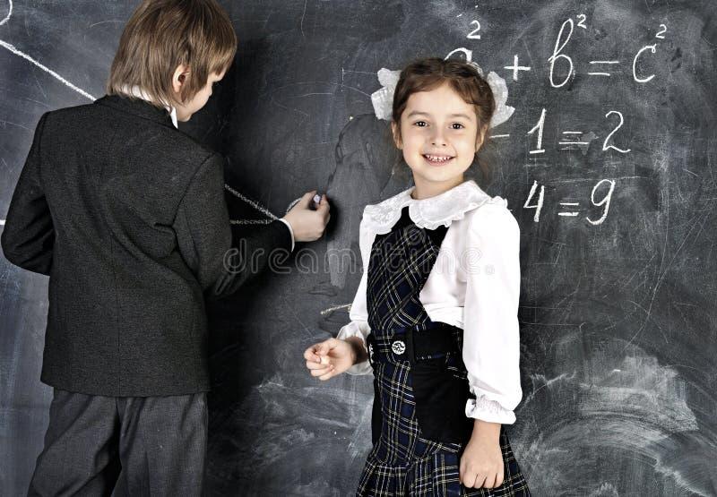 Escrita do menino e da menina no quadro-negro fotos de stock royalty free