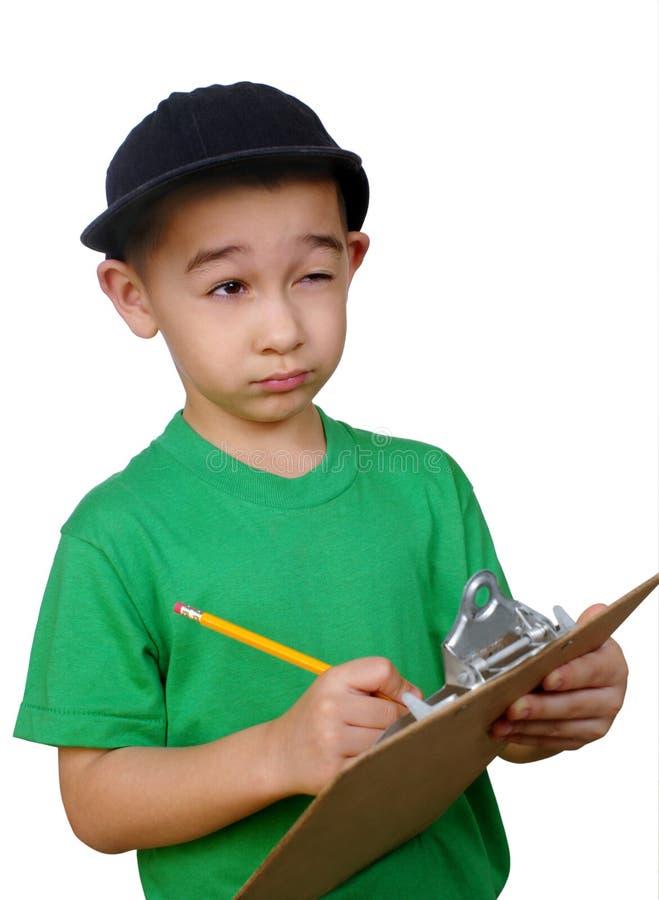 Escrita do menino em uma prancheta imagens de stock royalty free