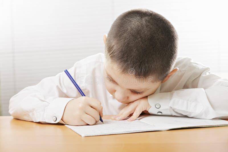 Escrita do menino que dobra-se sobre o copybook fotos de stock