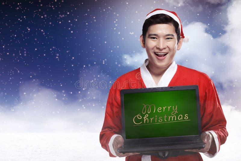 Escrita do Natal de Santa Claus Holding Laptop With Merry fotos de stock