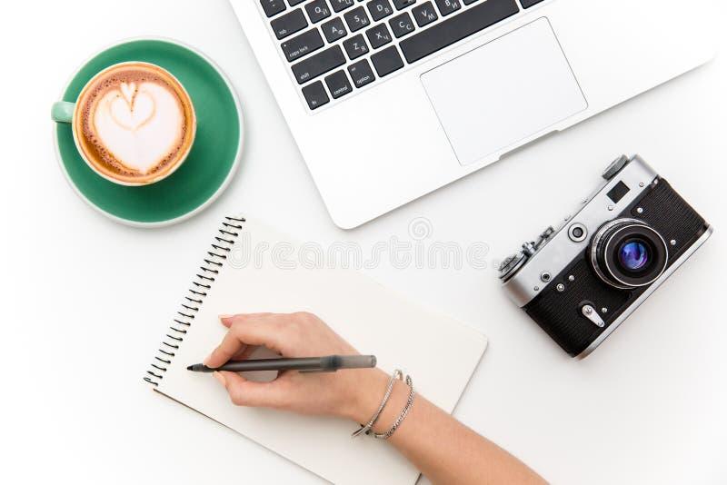 Escrita do portátil, da câmera, da xícara de café e da mão no caderno imagem de stock