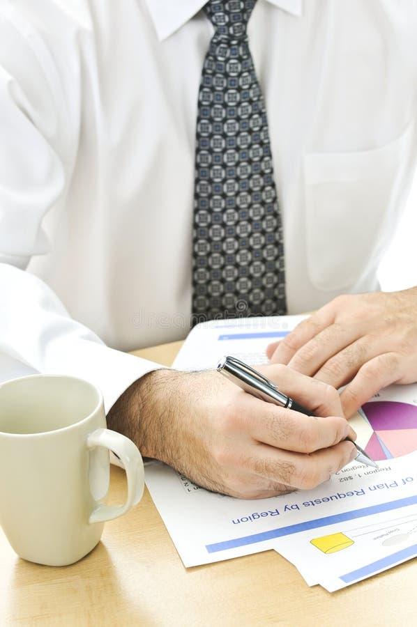 Escrita do trabalhador de escritório em relatórios imagem de stock