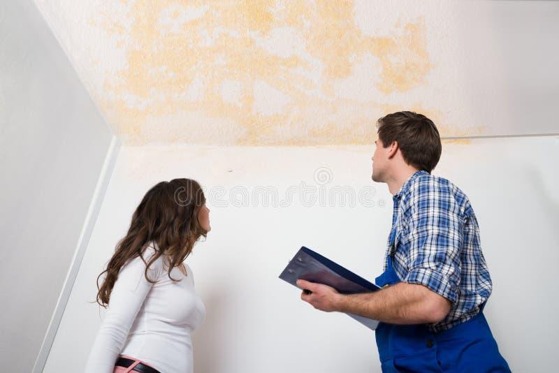 Escrita do trabalhador na prancheta com a mulher na casa imagens de stock royalty free