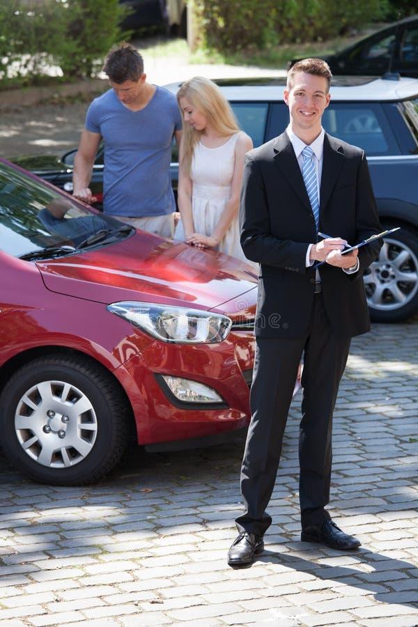 Escrita do vendedor na prancheta com os pares que olham o carro fotografia de stock royalty free