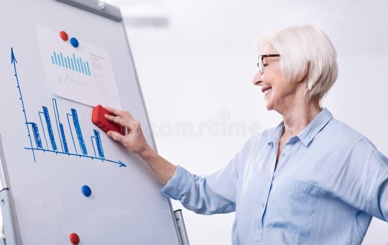 Escrita envelhecida da mulher de negócios que limpa a placa branca no escritório imagens de stock