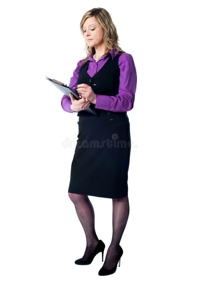 Escrita fêmea da secretária na prancheta fotos de stock