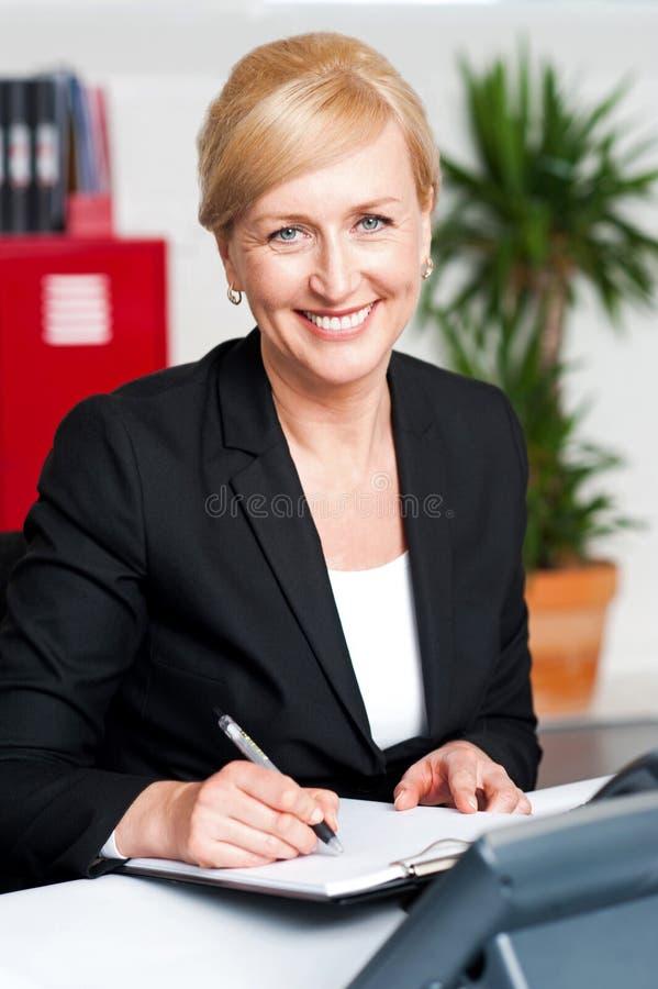 Escrita fêmea da secretária no bloco de notas foto de stock
