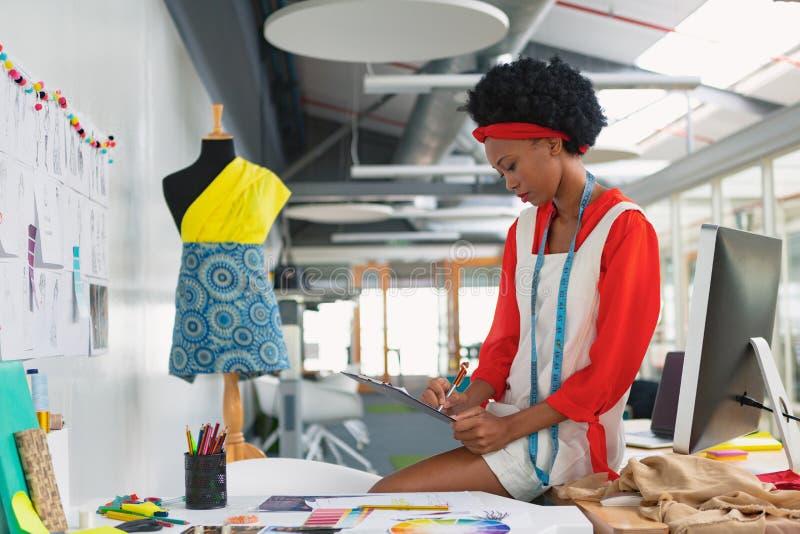 Escrita fêmea do desenhador de moda em uma prancheta na mesa imagem de stock