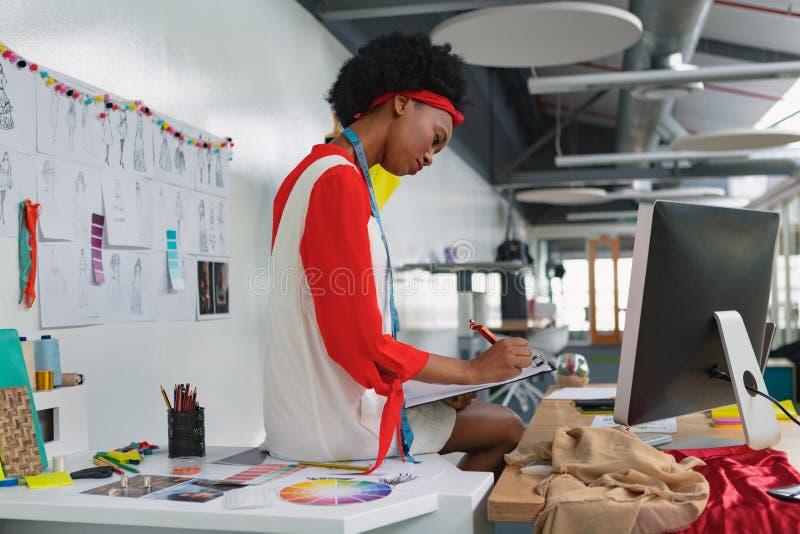 Escrita fêmea do desenhador de moda em uma prancheta na mesa foto de stock