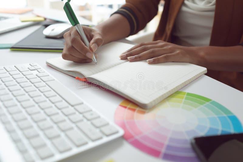 Escrita fêmea do designer gráfico no diário na mesa em um escritório moderno foto de stock