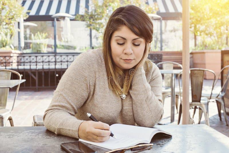 Escrita fêmea latino-americano em seu jornal em um café exterior imagens de stock royalty free
