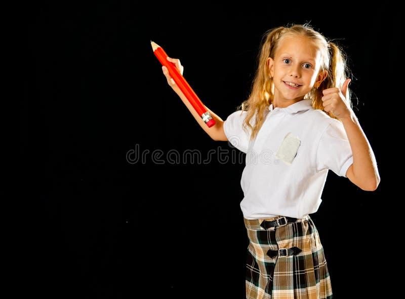 Escrita feliz da estudante no quadro-negro com o polegar acima do gesto fotografia de stock royalty free