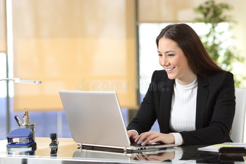 Escrita feliz da mulher de negócios no portátil no escritório fotos de stock