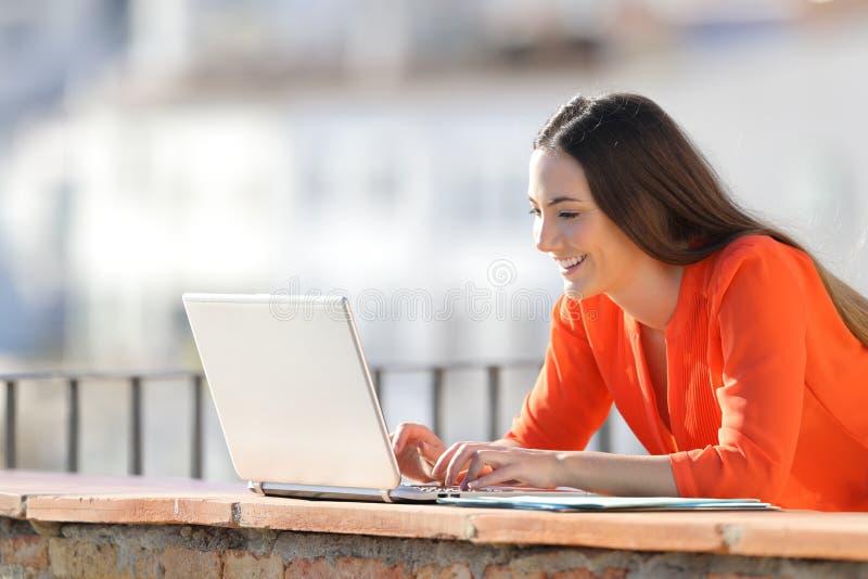 Escrita feliz do empresário no portátil em um balcão imagens de stock royalty free
