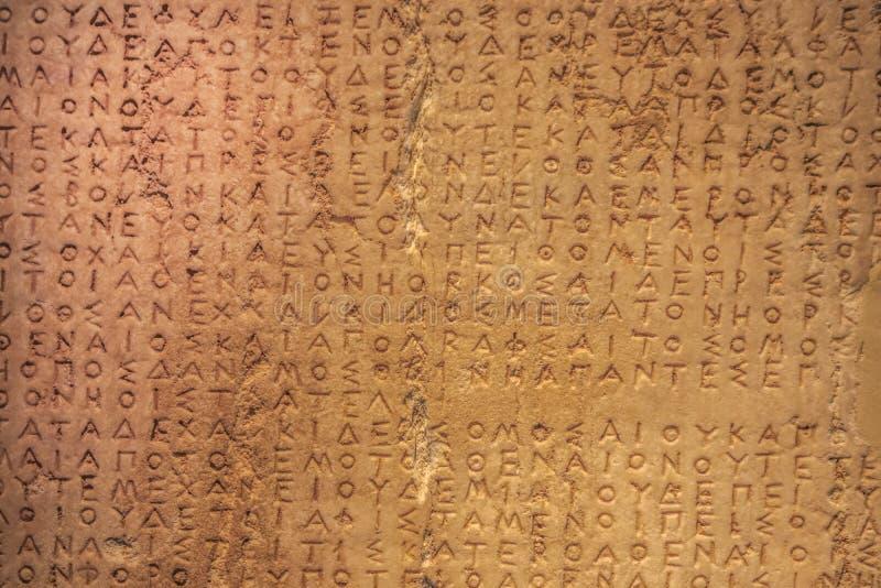 Escrita grega danificada velha muito textured cinzelada em uma pedra com quebras e dano e descoloração - áreas granulados onde da fotografia de stock royalty free