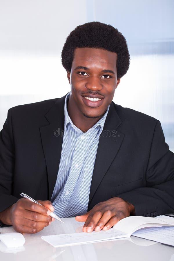 Escrita humana da mão no cheque fotografia de stock