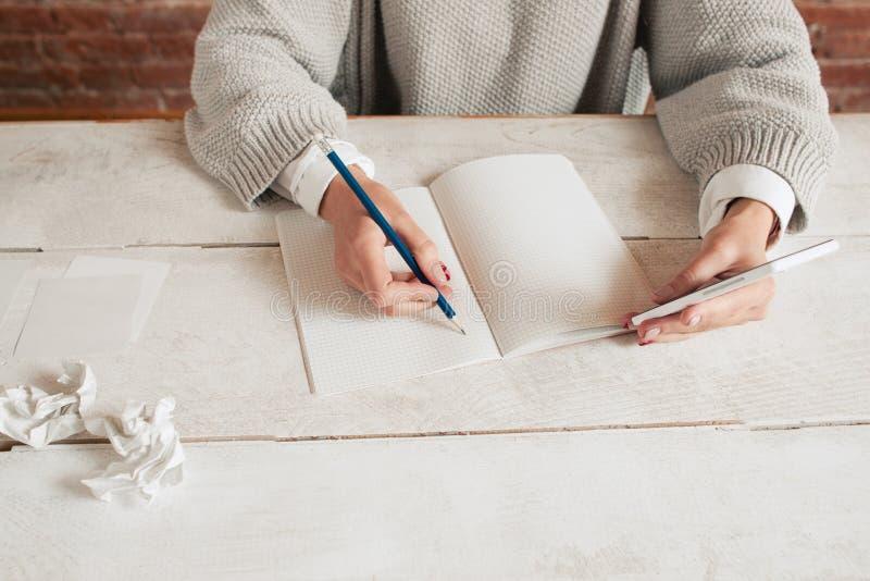 Escrita irreconhecível da mulher no modelo do caderno fotos de stock