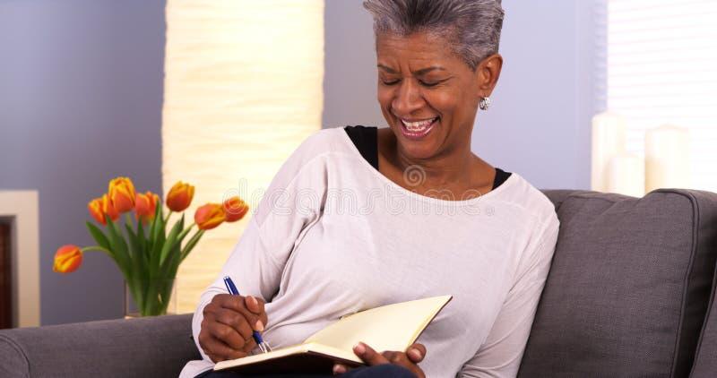 Escrita madura da mulher negra no jornal foto de stock royalty free