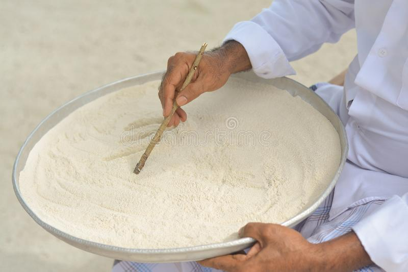Escrita maldiva do professor no dhivehi na areia usando a vara de madeira fotos de stock