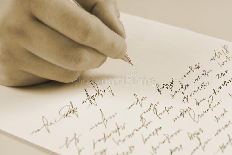 Escrita masculina da mão em um papel fotografia de stock