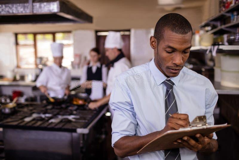 Escrita masculina do gerente em um clipbaord na cozinha fotos de stock