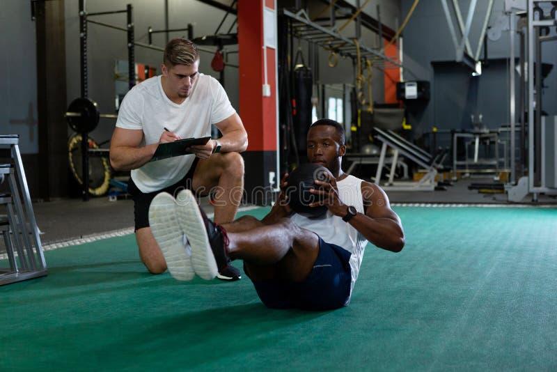 Escrita masculina do instrutor na prancheta quando exercício atlético masculino com bola do exercício imagem de stock royalty free
