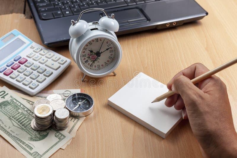 Escrita masculina do lápis do uso da mão do negócio na nota do papel e no local de trabalho do negócio dos objetos da finança do  fotografia de stock royalty free