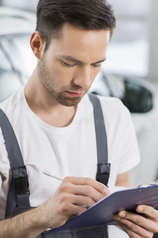 Escrita masculina do mecânico de automóvel na prancheta na oficina imagens de stock royalty free