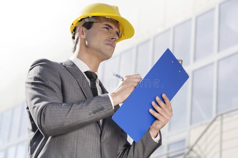 Escrita masculina nova do arquiteto na prancheta ao olhar a construção exterior ausente fotos de stock