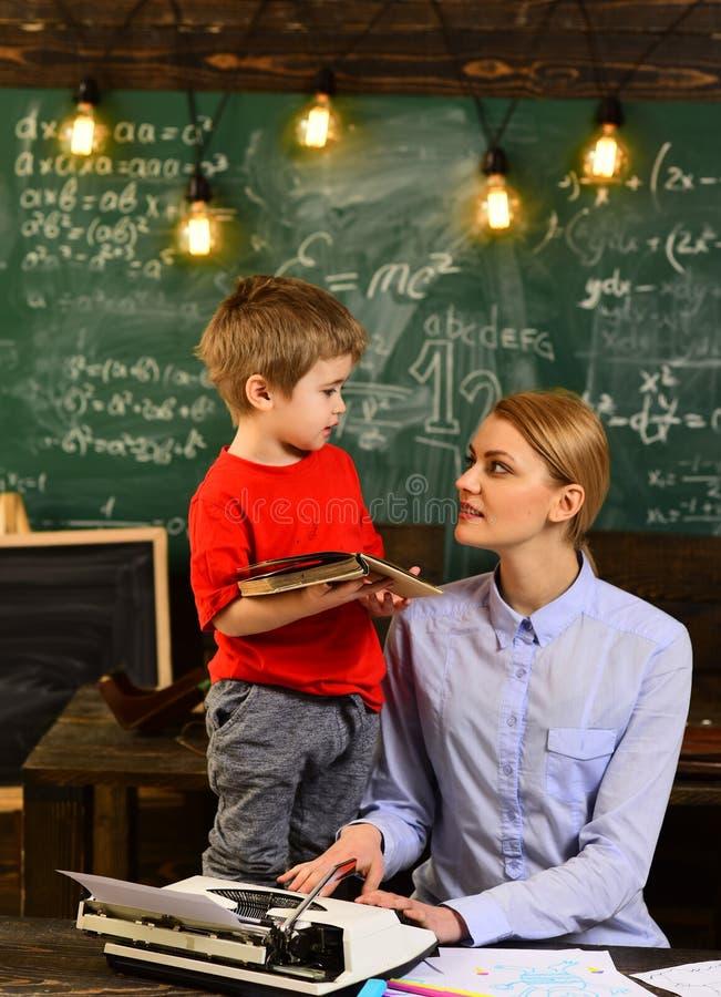 Escrita moderna do moderno do professor no quadro-negro grande com fórmula da matemática, tutor que senta-se ao lado da mesa dura imagem de stock royalty free