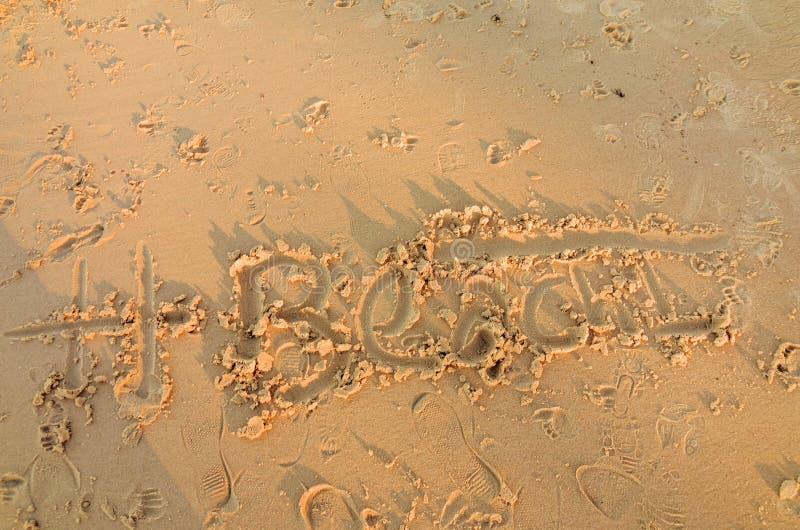 Escrita na areia da praia entre pegadas fotos de stock