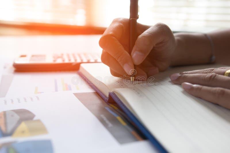 A escrita no caderno na tabela de madeira, finança do homem de negócios do conceito que aplana e analisa imagem de stock