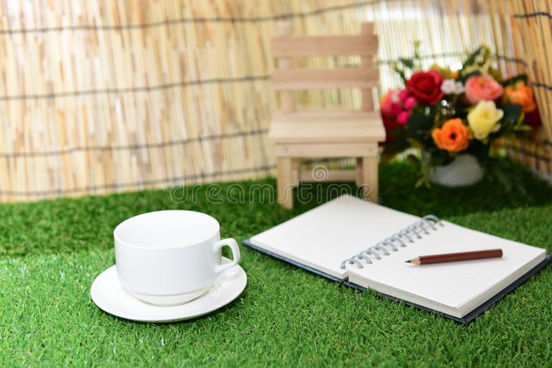 Escrita no livro de nota do espaço da cópia no fundo da grama verde Com s imagem de stock