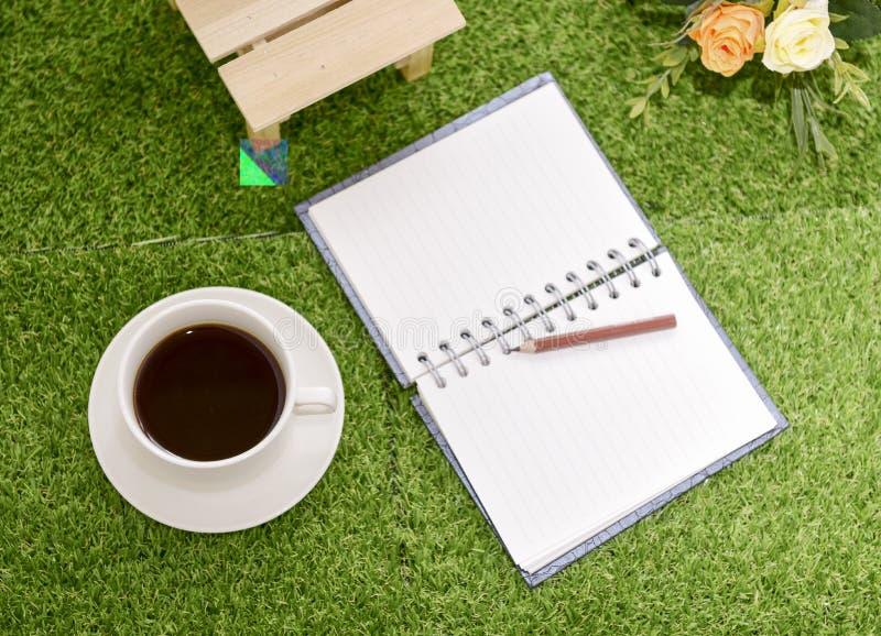 Escrita no livro de nota do espaço da cópia no fundo da grama verde Com s imagens de stock
