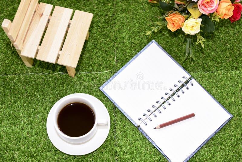 Escrita no livro de nota do espaço da cópia no fundo da grama verde Com s fotografia de stock royalty free