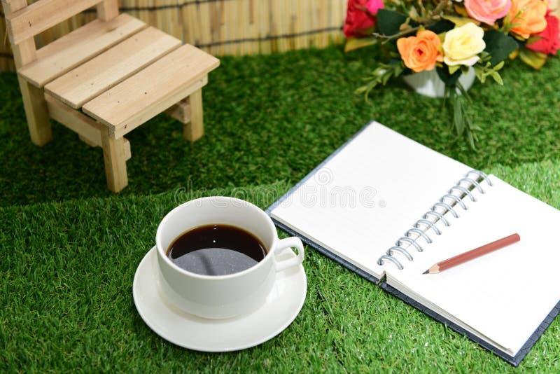 Escrita no livro de nota do espaço da cópia no fundo da grama verde Com s foto de stock