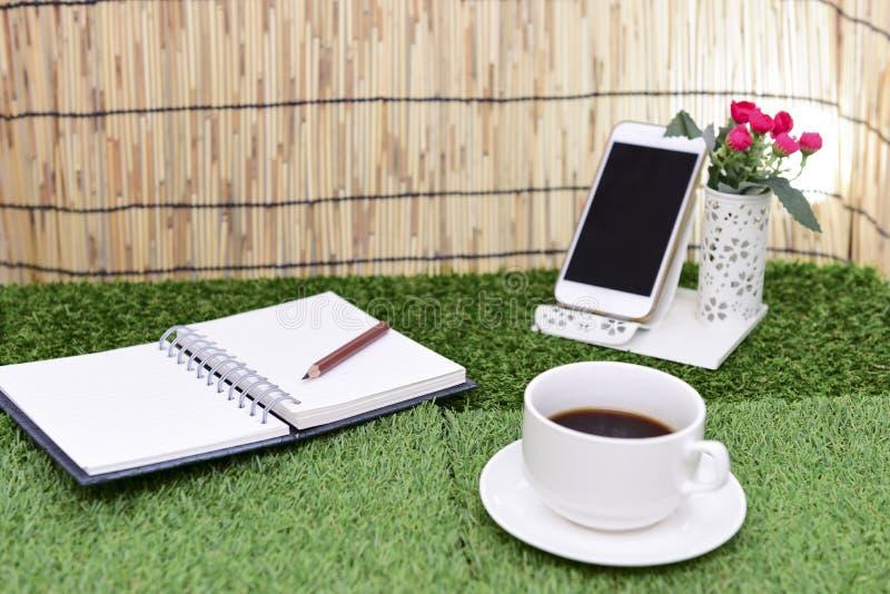 Escrita no livro de nota do espaço da cópia no fundo da grama verde Com s fotografia de stock