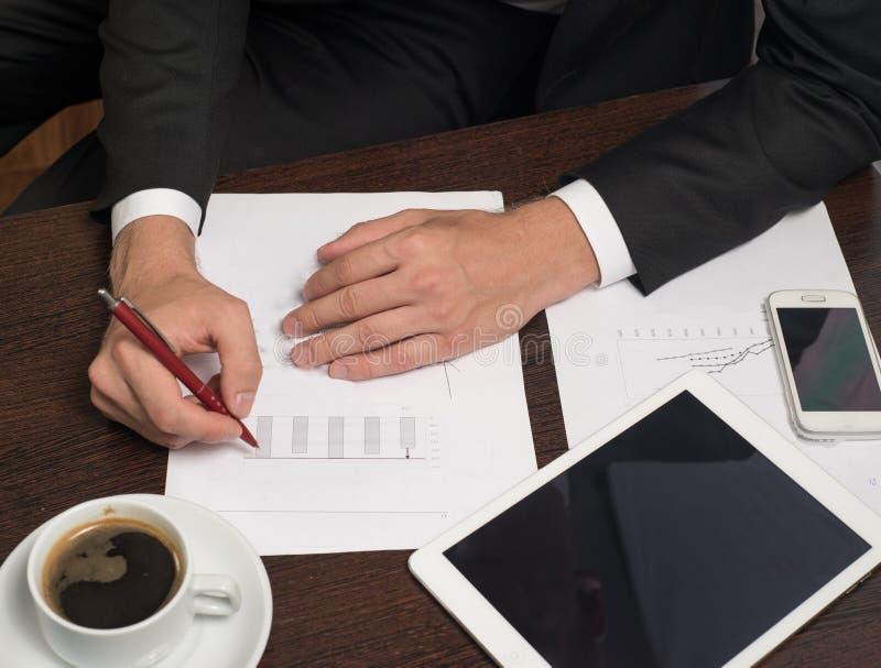 Escrita no papel ao lado da tabuleta, café do homem de negócios, telefone celular imagens de stock
