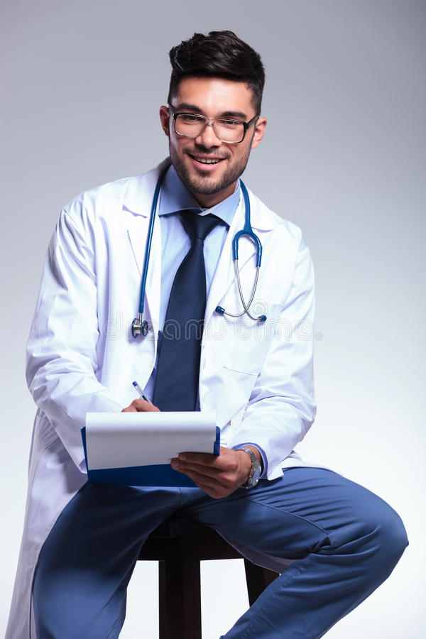 Escrita nova assentada do doutor na prancheta imagens de stock