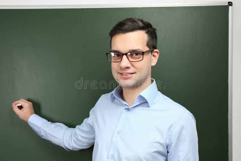 Escrita nova considerável do professor no quadro-negro imagem de stock