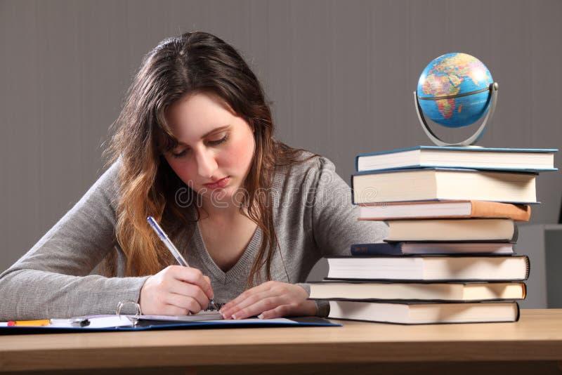 Escrita nova da menina do estudante com os livros em torno dela fotografia de stock