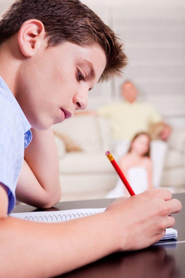 Escrita nova do adolescente em seu caderno fotos de stock