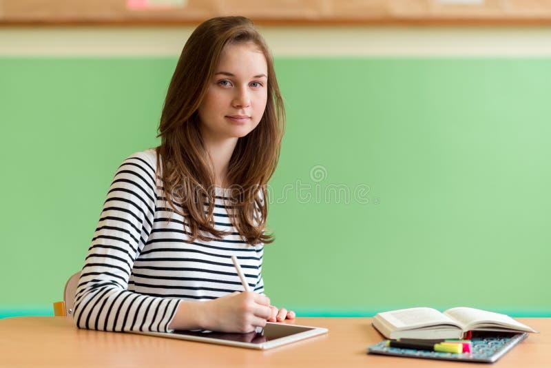 A escrita nova do estudante fêmea nota usando a tabuleta digital durante a classe Conceito da GERAÇÃO Z imagem de stock royalty free