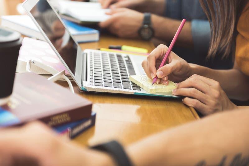 Escrita nova do estudante no papel pequeno durante a leitura imagem de stock