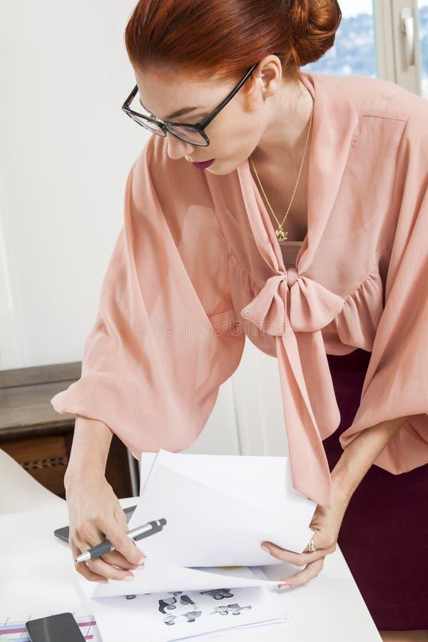 Escrita nova ereta da mulher do escritório em uma mesa foto de stock