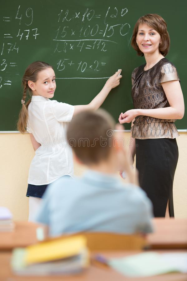 Escrita pequena da estudante no quadro-negro fotografia de stock